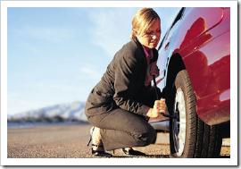 Mulher troca pneu furado
